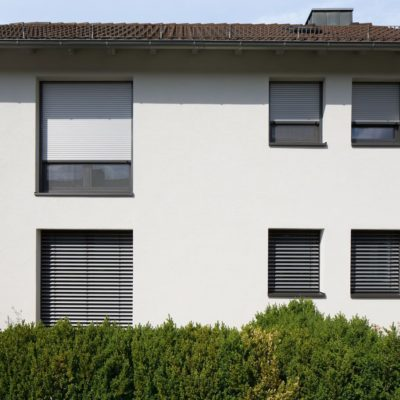 Weißes Haus und Rolllade an den Fenstern
